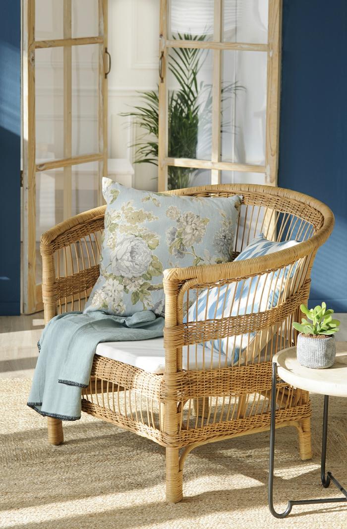 formation home staging, chaise en rotin, coussins vintage, murs en bleu foncé, petite table ronde en bois et fer forgé