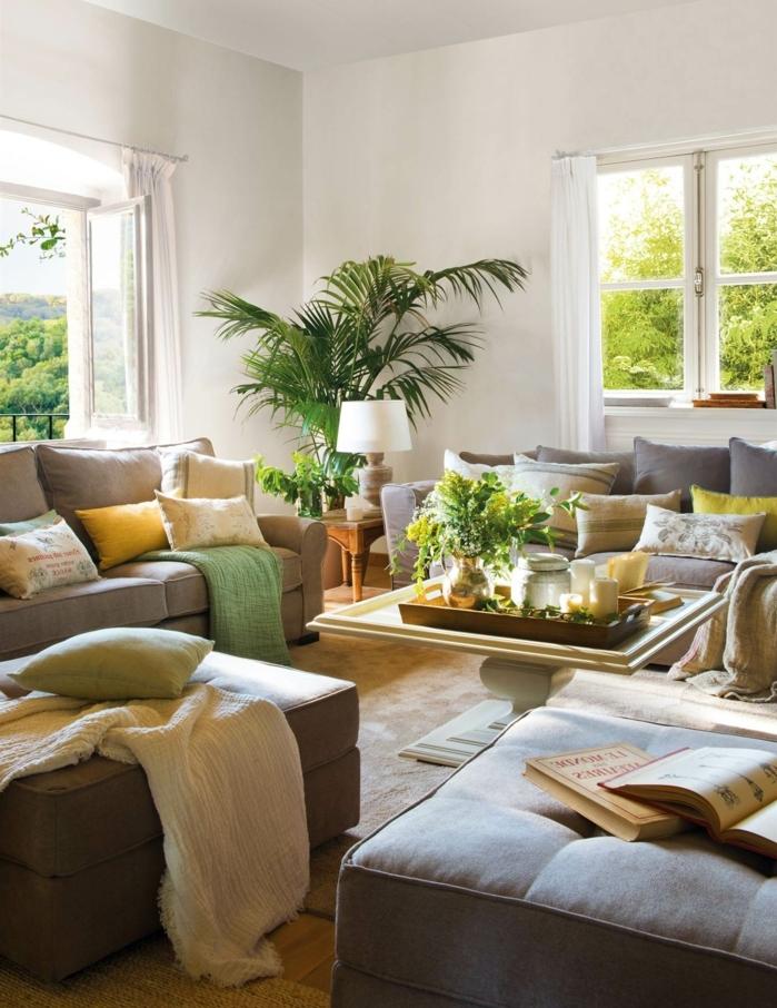home staging, murs blancs, canapé en gris, plaid moelleux en blanc, coussins en jaune, livres, grandes fenêtres