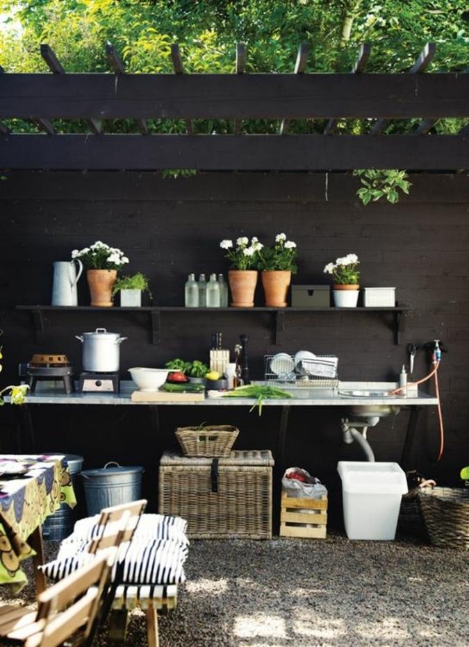 une pergola en bois foncé équipée d'un coin repas, cuisine d'été sommaire