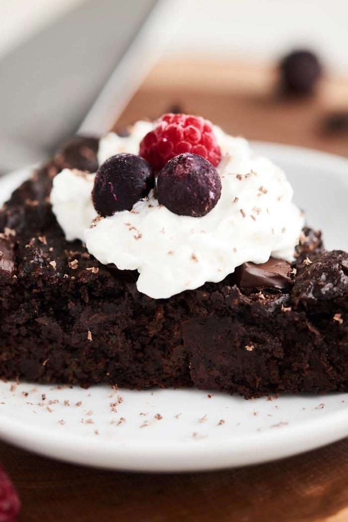 comment préparer un gâteau sans oeufs, exemple de morceau de gâteau au chocolat noir avec décoration en crème blanche et fruits