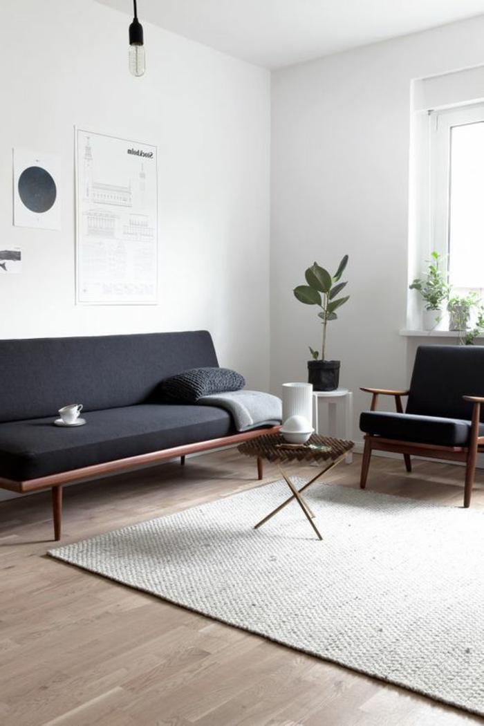 intérieur minimaliste, sofa noir style mid century, murs blancs, tapis gris clair