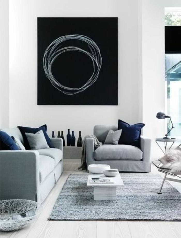 intérieur minimaliste, sofas gris, tableau noir au mur, tapis gris, plusieurs coussins