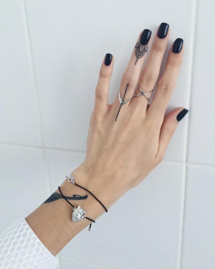 un petit tatouage à lotus sur le bout du doigt, idée pour un tatouage féminin