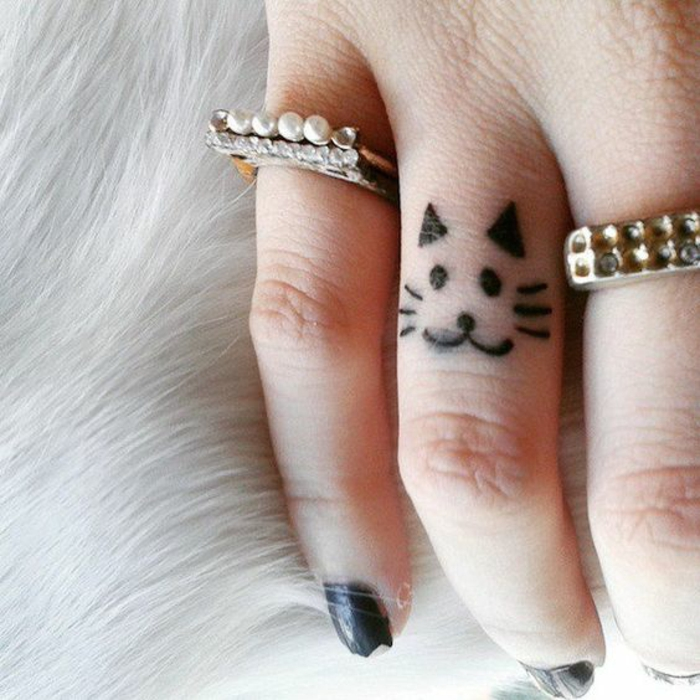 un adorable tatouage sur le doigt à motif chat, dessin simple et