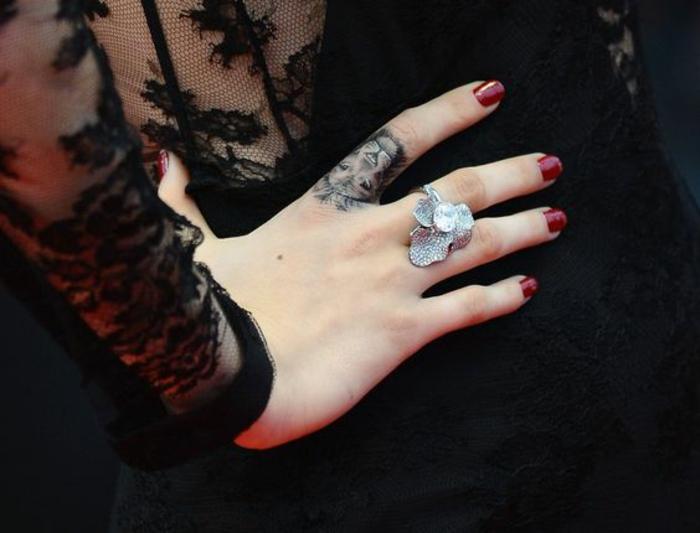 un tatouage main original réalisé sur le doigt, tatouage lion qui fait office de bague