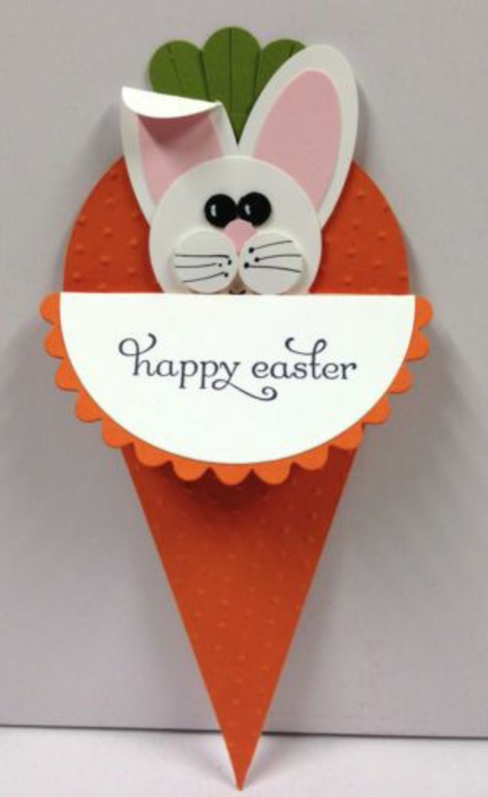 lapin de paques blanc, des oreilles rose, dans une carotte en papier orange, idée originale de carte joyeuses paques, activité manuelle printemps