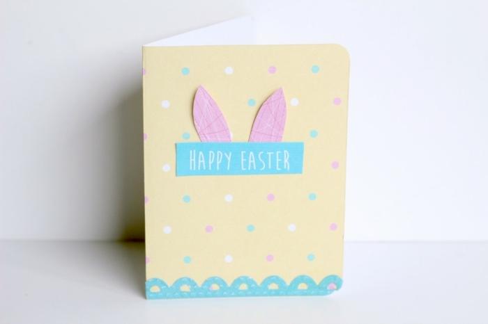 carte pour souhaiter joyeuses paques, fond jaune, points multicolores, oreilles de la pin de paques rose, bordure bleue, souhait