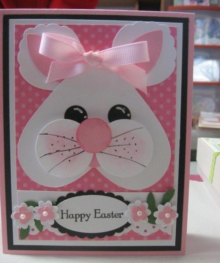 carte de paques, fond rose à petits points blancs, bonne fete de paque, fleurs en papier, tete de lapin de paques en blanc, ruban rose