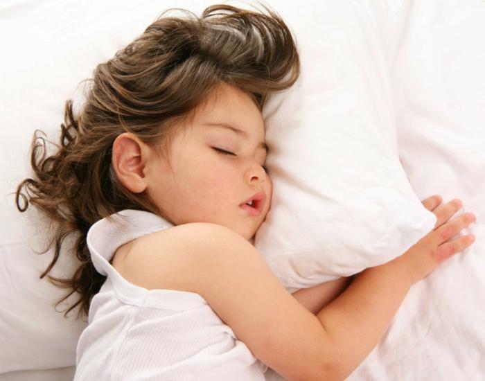 matelas nid douillet, fille endormie, cheveux brunes, linge de lit blanc