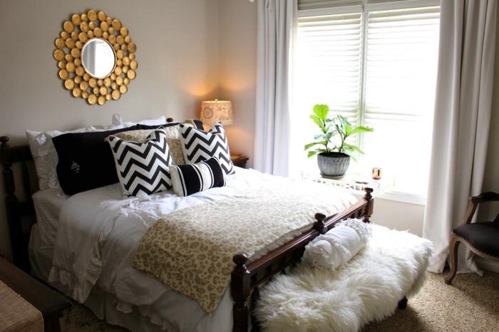 matelas nid douillet, plaid en fausse fourrure, miroir rond, coussins décoratifs, plantes vertes