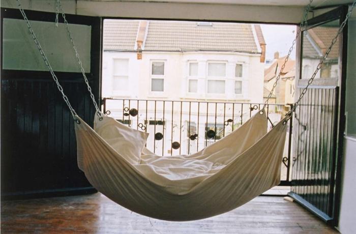 le nid douillet, lit imitation hamac, grandes portes vers le balcon, parquet en bois