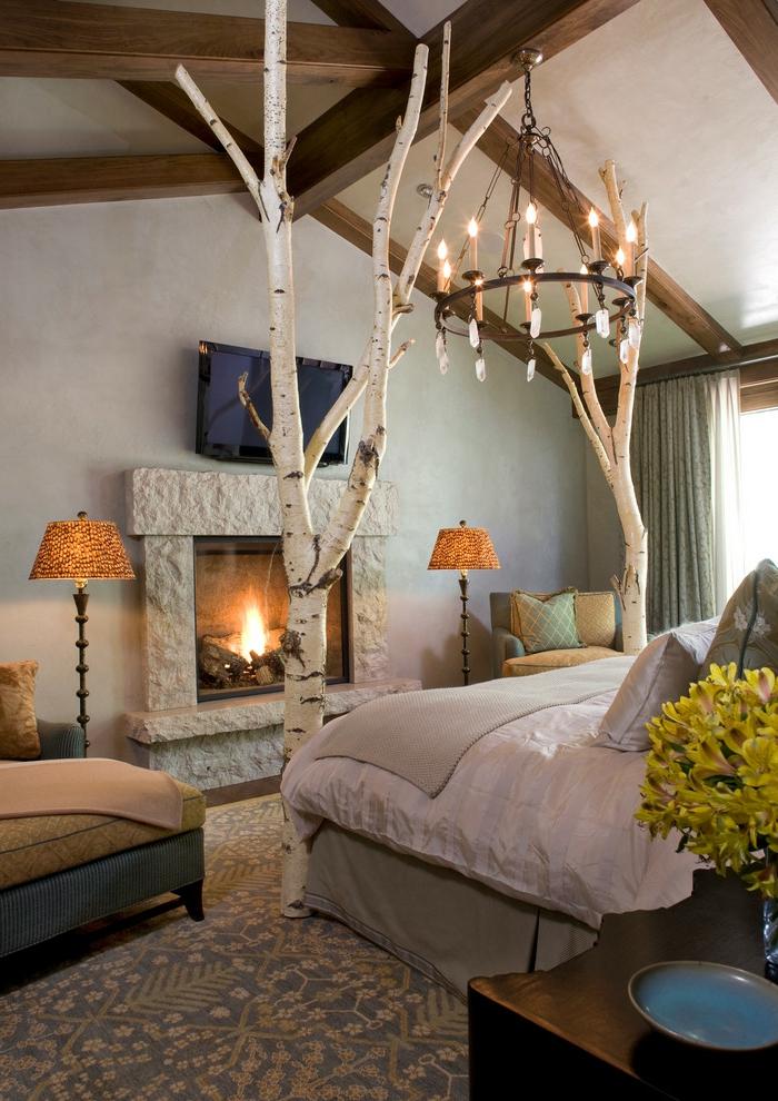 lit douillet, cheminée en pierre, grand lit, coussins décoratifs, fauteuil beige, lustre à bougies