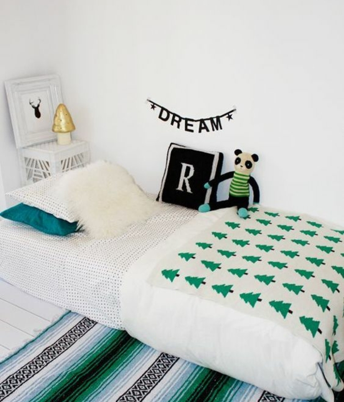mur couleur blanche, tapis rayures blancs, noirs, couverture de lit motifs sapins, coussin monogrammé, cossins multicolores, jouet panda