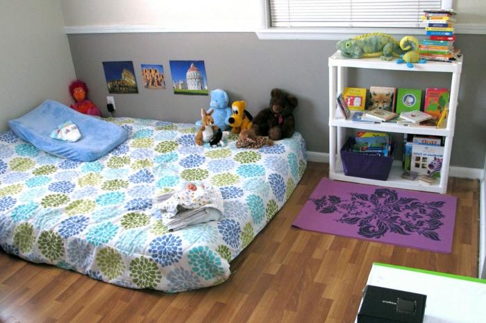 lit bébé matelas à motifs floraux, parquet, rangement livres, jouets, deco murale photo, curiosités, couleur mur en gris et blanc