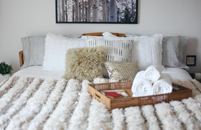 le nid douillet, plaid en fausse fourrure, coussins décoratifs, tête de lit en bois