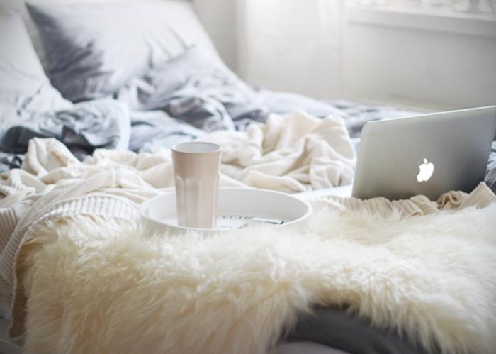 le nid douillet, tasse de café, notebook, linge de lit gris, plaid en fausse fourrure