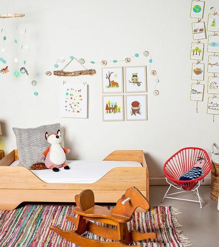 couleur peinture blanche, lirt en bois sur le sol, matelas blanc, jouet renard, chaise à bascule, tapis multicolore, deco murale dessins, méthode montessori chambre enfant