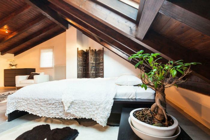 lit en bois, linge de lit, couverture de lit blanc, plante, paravent motifs orientaux, commode en bois, fauteuil blanc