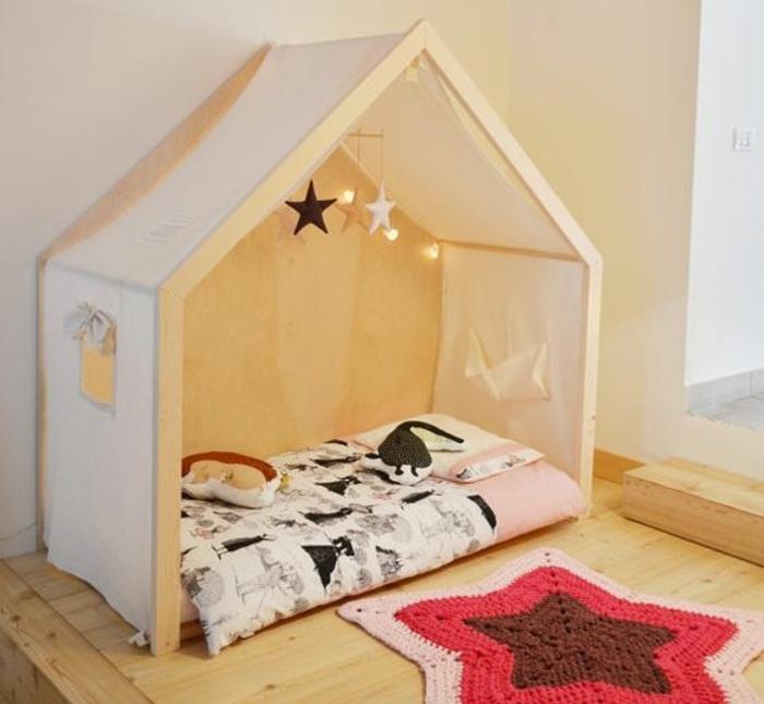 mur couleur blanche, maisonnette en bois, voiles, matelas, couverture de lit noir et blanc, tapis tricot en forme d étoile, parquet clair