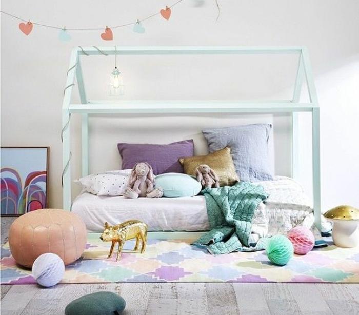mur couleur blanche, maisonnette vert clair, matelas, coussins multicolores, tapis multicolore, pouf, guirlande à coeurs, pédagogie montessori amenagement chambre