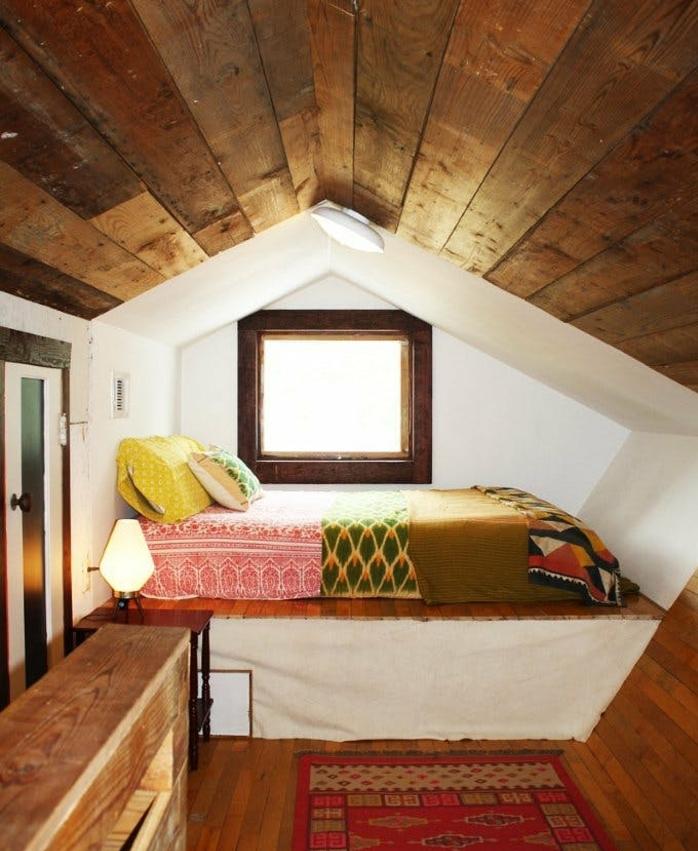 toiture planche de bois, matelas en hauteuil, linge de lit multicolore, motifs orientaux, tapis oriental, commode en bois, amenagement combles