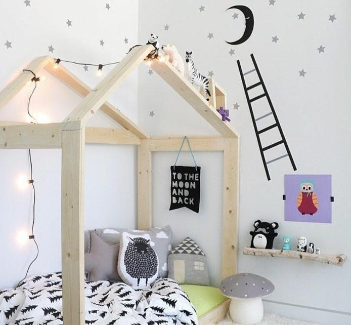 chambre montessori avec lit montessori en bois, types maisonnette, couverture lit blanc à sapins noirs, peinture mur blanche, stickers ciel étoiles, lune, coussins, petits jouets