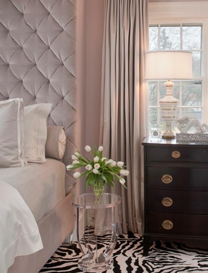 lit rose avec une tete de lit capitonée et linge de lit blanc, commode en bois vintage,tapis zèbre, rideaux rose, peinture chambre adulte rose