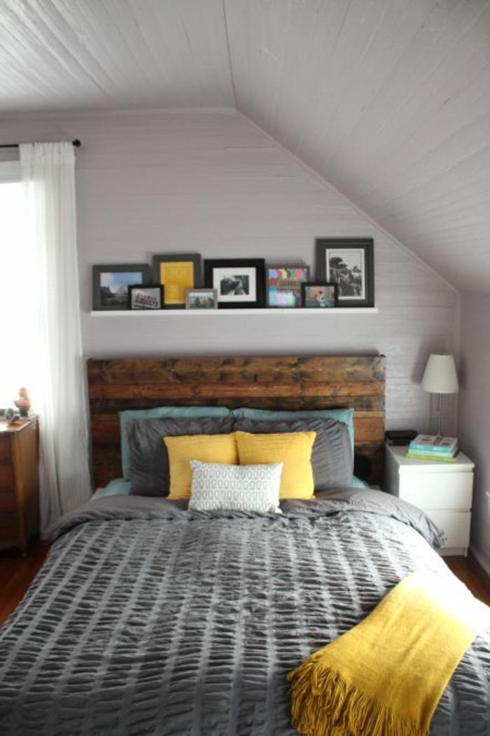 amenagement combles, lit en bois brut, linge de lit gris, couverture et coussins jaunes, coussins bleu et gris, etagere murale, photos, couleur mur blanc