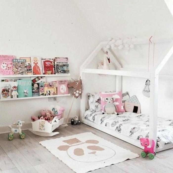 amenagement chambre bébé selon la méthode montessori, tapis panda, lit maisonnette blanche, etageres rangement livres, coussins