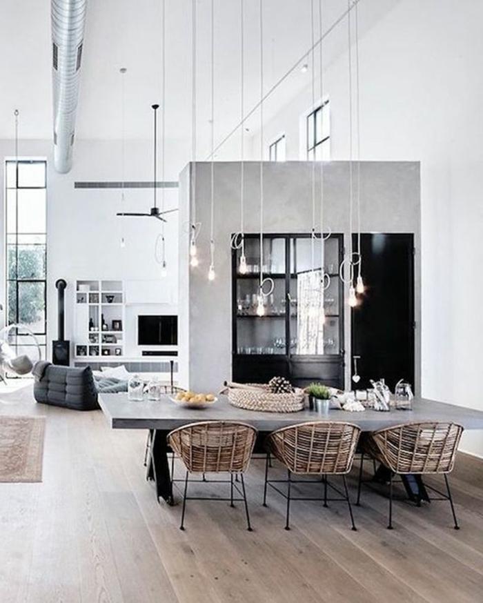 maison minimaliste, grande table en béton ciré, chaises tressées, ampoules pendantes