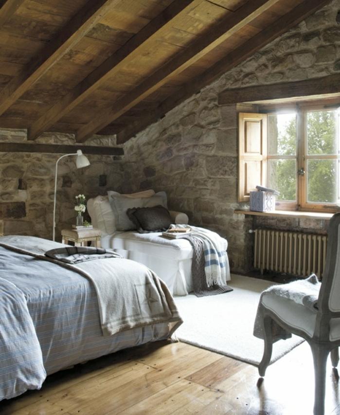 amenagement comble, mur en pierres, charpente toit en bois, linge de lit gris, tapis blanc, chaise vintage, idée déco chambre rustique chic