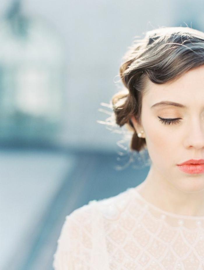 look de mariée romantique réalisé avec une coiffure rétro et un maquillage léger nude pêche