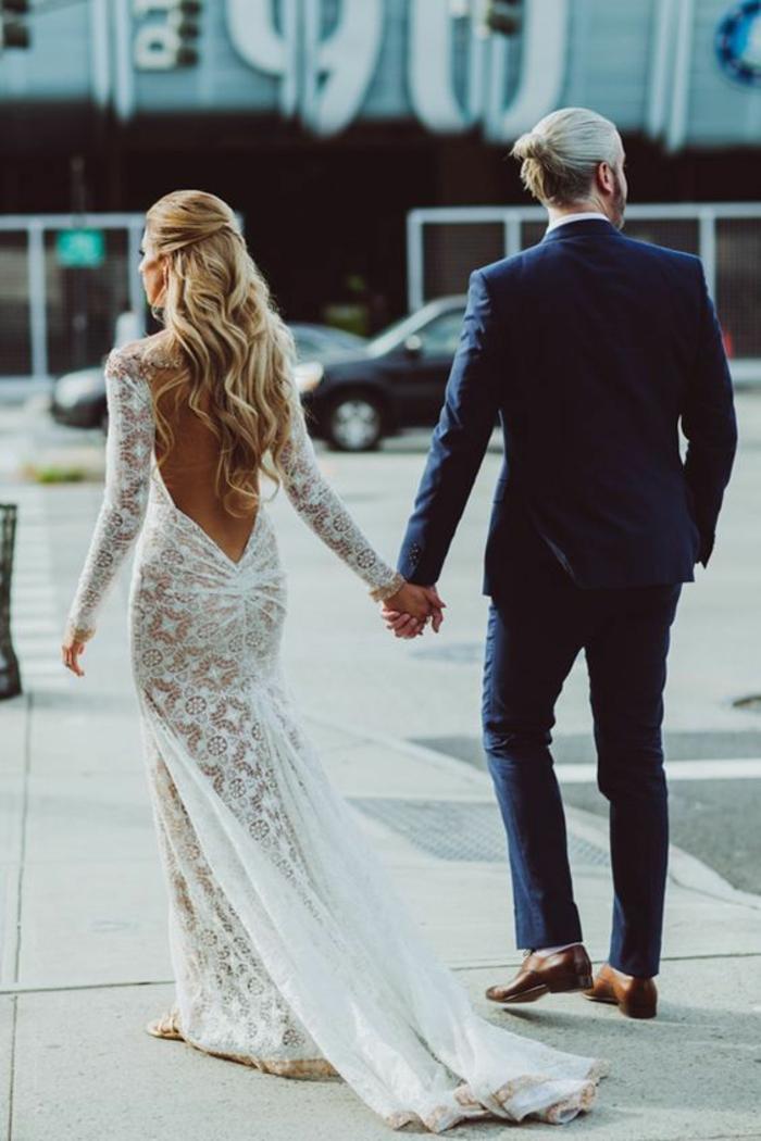 une jolie robe de mariée moulante à manches longues et à traîne, modèle à dos nu