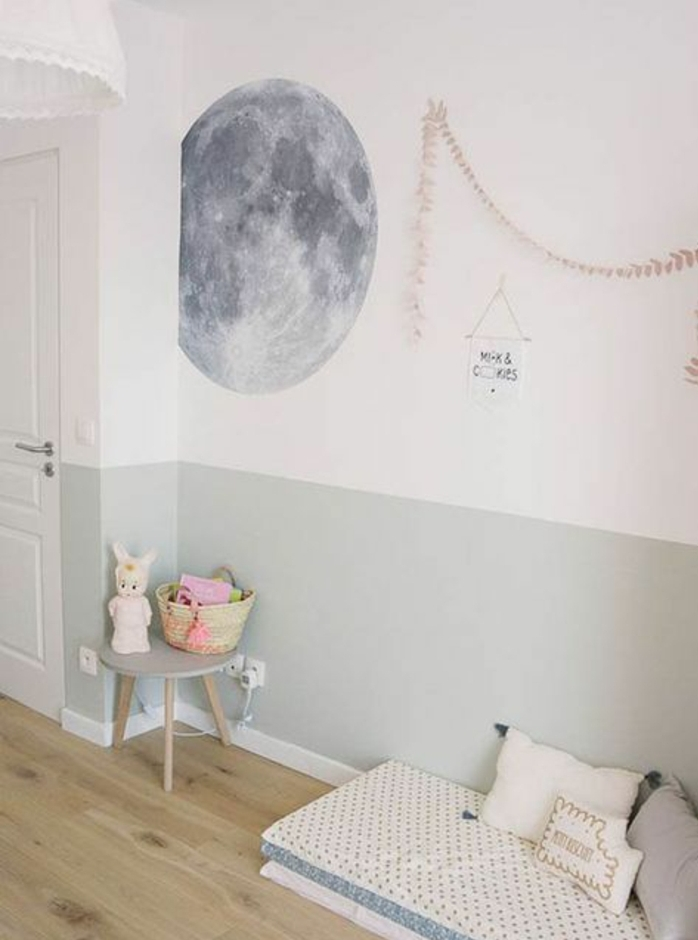 exemple chambre montessori, parquet clair, matelas, coussins gris et blanc, mur couleur blanche et grise, jouet, lune sticker mural