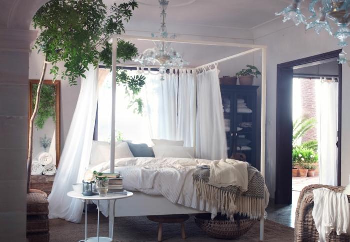 lit douillet, plantes vertes, lit à baldaquin, plaid avec franges, fauteuil en paille, couverture blanche