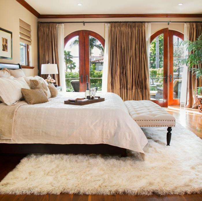 comment faire un lit au carré, tapis en fausse fourrure, banc devant le lit, rideaux longs