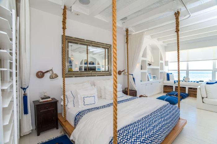 bleu grec, lit suspendu, grand miroir, tapis bleu foncé, couverture de lit en blanc et bleu
