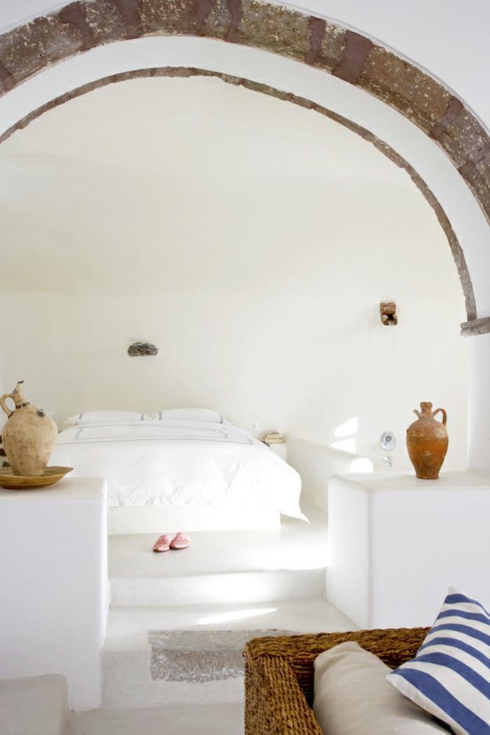 bleu grec sur les coussins, arc en pierre, murs blancs, vase ancienne