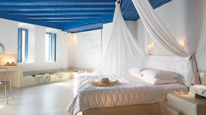 décoration grecque, sol en marbre, miroir rond, bougies, volets bleu clair, lit à baldaquin