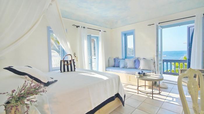 décoration grecque, lit à baldaquin, fleurs séchées, table ronde, volets bleus