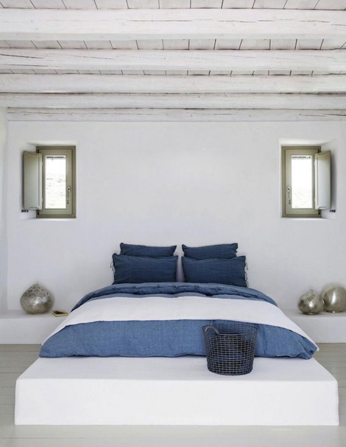 bleu grec sur le lit, petits volets en vert, plafond en bois, murs blancs