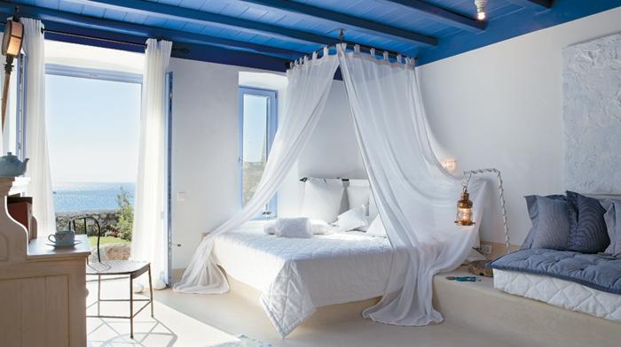 bleu grec sur le plafond en bois, lanterne à bougies, rideaux longs, lit à baldaquin