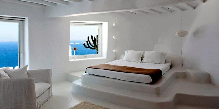 décoration grecque, murs blancs, plafond avec poutres en bois, lit surélevé, vue sur la mer