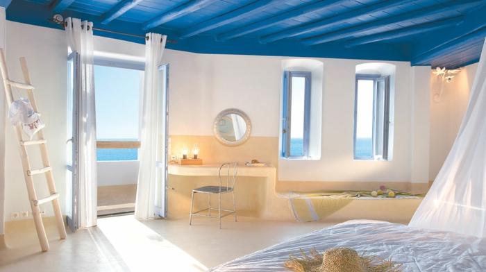 décoration grecque, plafond avec poutres en bois coloré en bleu, miroir rond, rideaux blancs