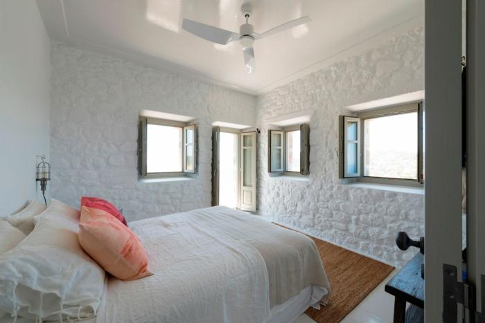 décoration grecque, murs blanchis à la chaux, volets kaki, ventilateur de plafond, tapis marron