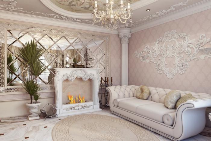 salon baroque, lustre en cristaux et bougies, plafond avec déco en plâtre, grand miroir, canapé blanc, tapis rond