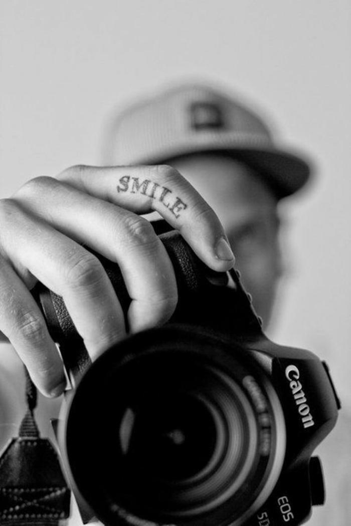 un tatouage main citation qui fait sourire, tatouage minimaliste sur le côté du doigt