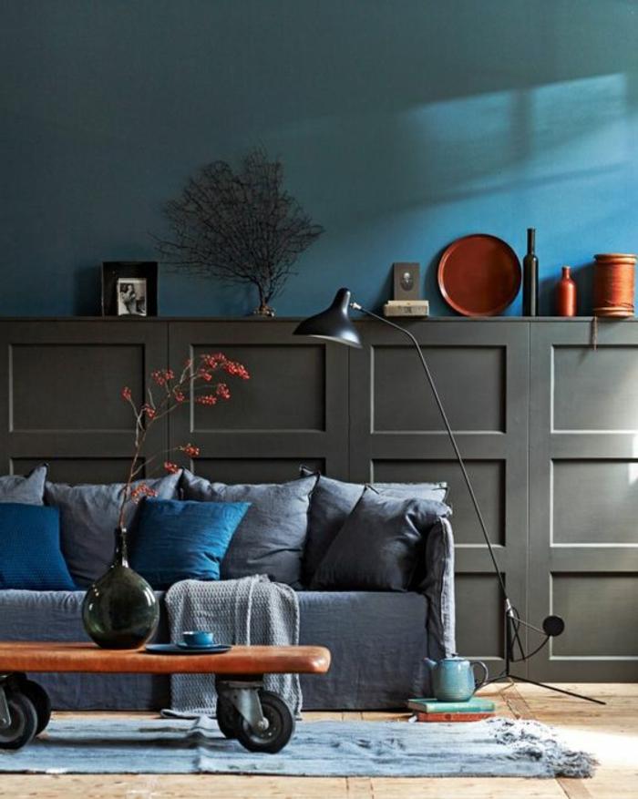 mur bleu canard, sofa gris avec coussins, table industrielle, lampe de sol