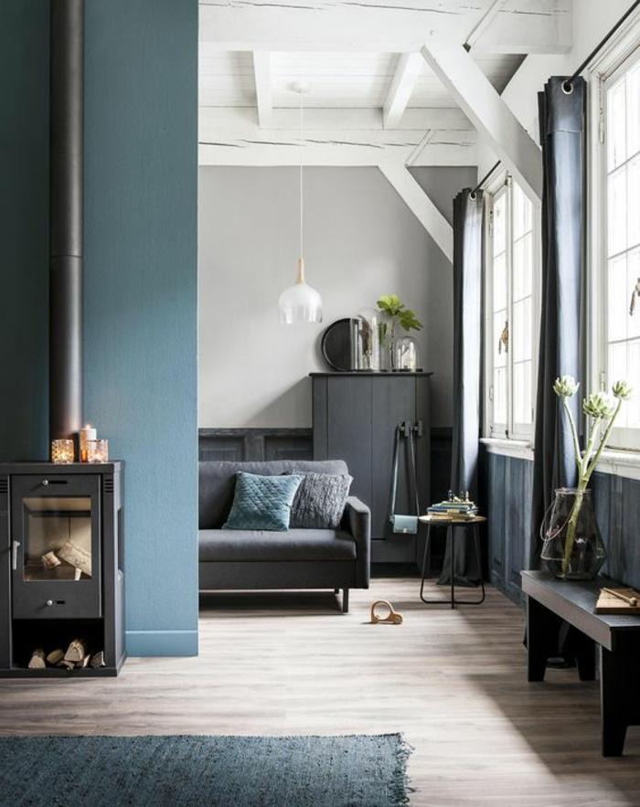 mur bleu canard, un poêle vintagen plafond blanc avec poutres apparentes, banquette noire