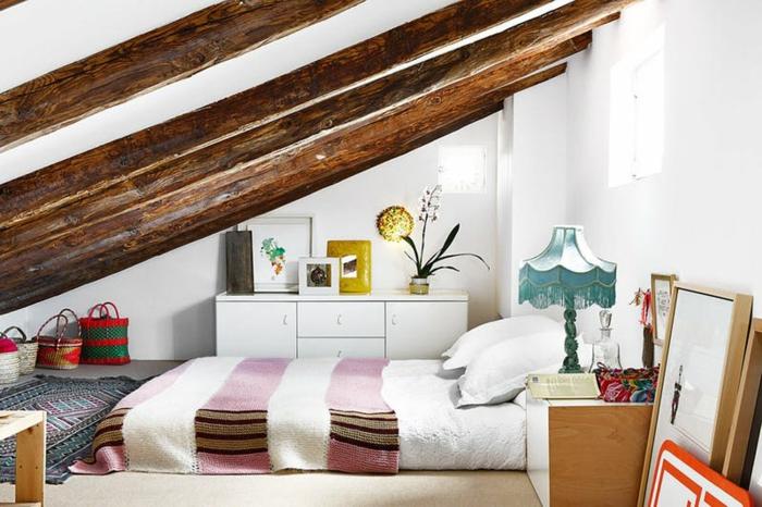 amenagement combles style bohème, matelas blanc, taies oreiller blanches, couverture de lit blanche à rayures rose, tapis oriental, poutres apparentes, meuble sous pente blanc
